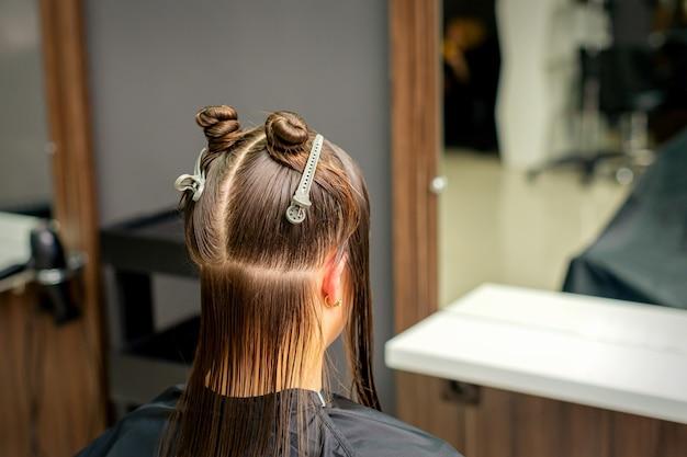 이발소에서 클립으로 여성의 머리카락을 섹션으로 나눴습니다.