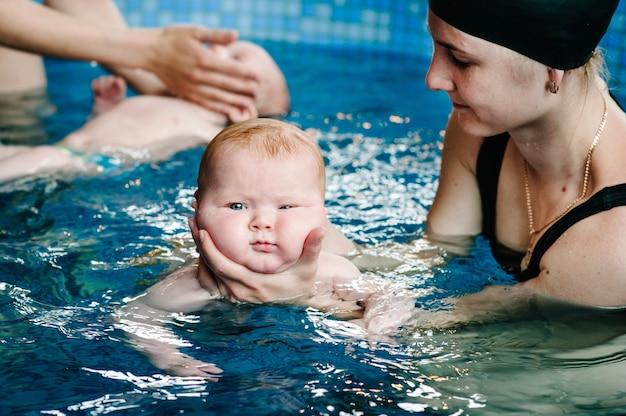 Ныряние с младенцем в детский бассейн. молодая мать, инструктор по плаванию и счастливая маленькая девочка в бассейне. научите ребенка плавать. наслаждайтесь первым днем купания в воде. мать держит ребенка и ныряет