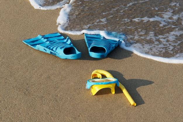 Дайвинг очки, трубка и ласты на пляже с мягкой океанской волной.