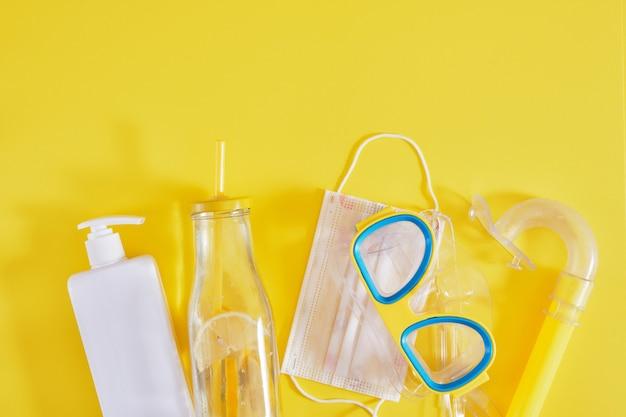 Маска для дайвинга, защитная медицинская маска, солнцезащитный крем и бутылка лимонада туризм во время пандемии коронавируса