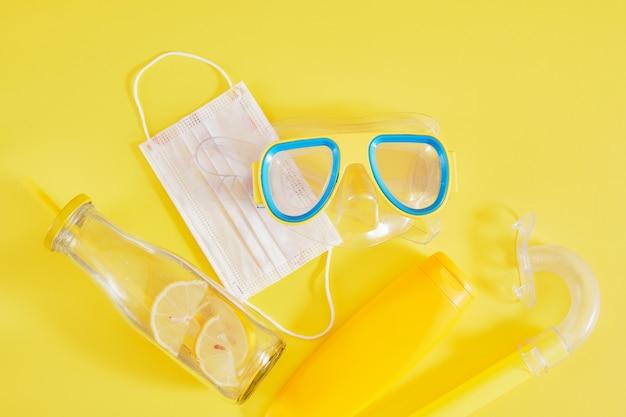 Маска для дайвинга, защитная медицинская маска, крем для загара и бутылка лимонада, концепция пляжного отдыха взаперти