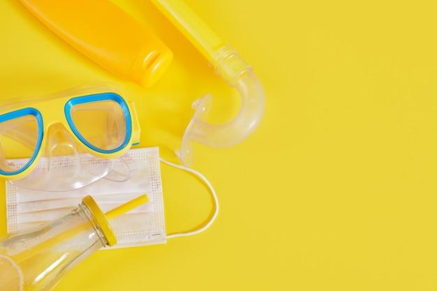 Маска для дайвинга, защитная медицинская маска, крем для загара и бутылка лимонада на желтом фоне, концепция пляжного отдыха взаперти