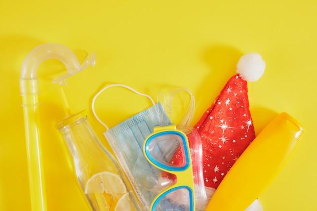 Набор для дайвинга, защитная медицинская маска, шляпа санта-клауса, крем для загара и бутылка лимонада на желтом фоне