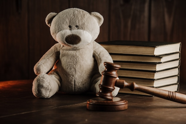 Divorce and alimony concept. wooden gavel and teddy bear as symbol of child on a desk
