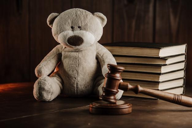 Понятие развода и алиментов. деревянный молоток и плюшевый мишка как символ ребенка на столе