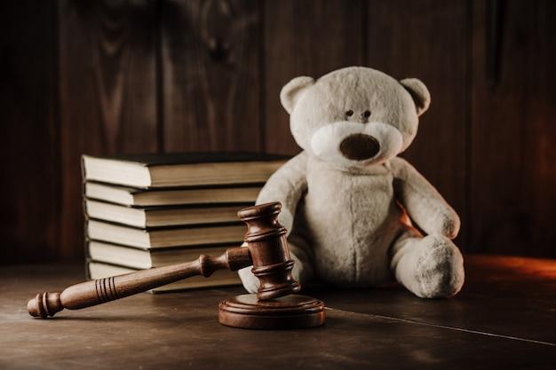 Понятие развода и алиментов. деревянный молоток и плюшевый мишка как символ ребенка