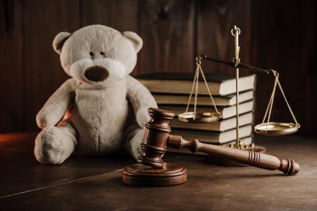 離婚と扶養手当の概念。公証人の役所で木製のガベルとテディベア