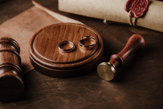 離婚の概念。公証人の公証人のガベルと金の指輪のクローズアップ裁判官