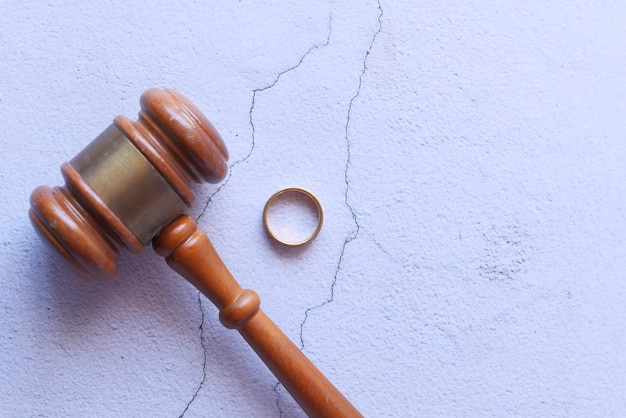 Divorce concept with gavel and wedding rings on table.