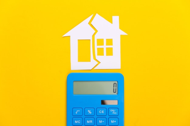 Divorce, property division concept. split paper house and calculator on yellow