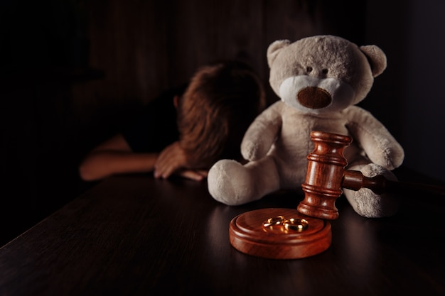 Divorce and separation concept. wooden gavel, rings and sad little boy with teddy bear. family law.