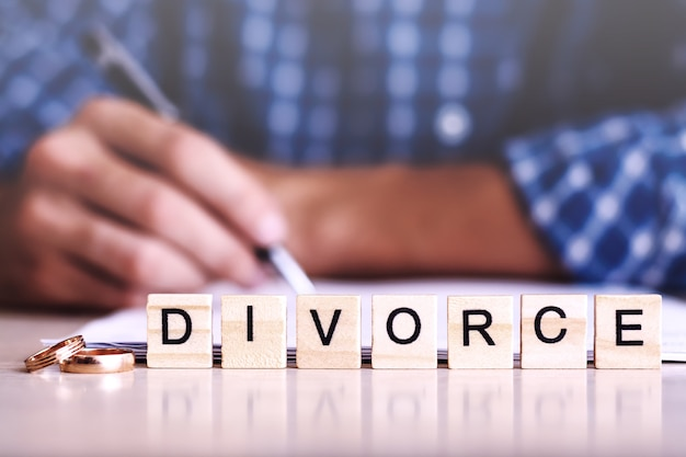 Divorce. word from wooden letters with rings and a man signing the agreement on the background