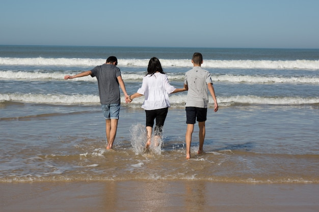 Divorced mother having fun with her two teenage boy on the beach