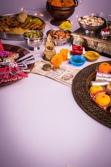 Дивали и подготовка к лакшми или лакшми пуджа с такими элементами, как дия, денежные купюры, сладости, цветы, закуски, халди и кумкум