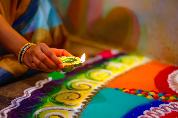 Дивали или праздничный свет. традиционный индийский фестиваль дивали, руки женщины держат масляную лампу