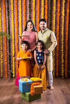 ディワリ祭またはラクシャバンダン祭-甘いラドゥー、石油ランプまたはディヤとギフトボックスでディーパバリまたはバイドゥージ祭を祝う4人のインドの若い家族、食べ物を食べる、または自撮りする