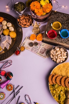 Diwali and preparation for laxmi or lakshmi pooja with elements like diya, currency notes, sweets, flowers, snacks, haldi and kumkum