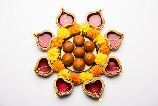 Diya 또는 오일 램프, 꽃 및 gulab jamun을 사용하여 흰색 장면 위에 배열된 diwali rangoli, 선택적 초점