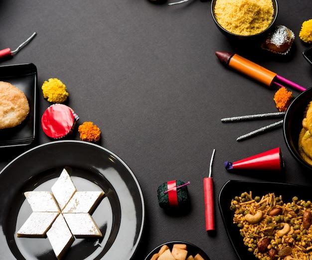 Сладости и закуски дивали, расположенные в группе с дийей или масляной лампой, цветами и огненными крекерами или патахе на мрачной поверхности, выборочный фокус