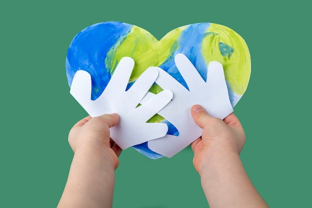 Diyと子供の創造性の概念。ステップバイステップの説明。紙からアップリケを作る。ステップ4子供の手が完成したクラフトの地球をハートの形で持っています。世界地球の日
