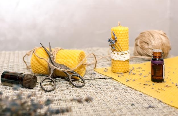 Аксессуары для изготовления восковых свечей своими руками: восковая тарелка, ножницы, джут, ароматическое масло, сухоцветы.