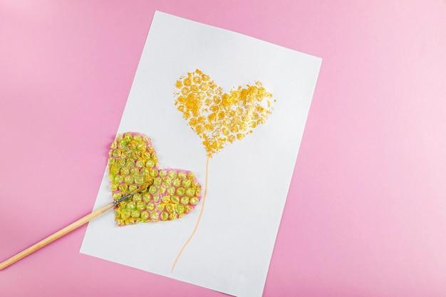 Diyと子供の創造性バブルラップを使用してハートでグリーティングカードを描くバレンタインの女性と母の日のための子供たちの工芸品非標準の非伝統的な描画方法
