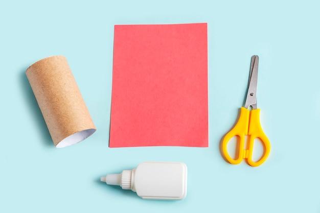 Diyと子供の創造性。トイレットペーパーのチューブからタコを作ります。準備ツールはさみ、接着剤、紙
