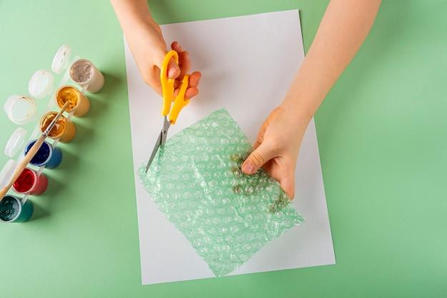 Diyと子供の創造性ステップバイステップの説明バブルラップを使用してグリーティングカードを描くステップの子供の手はバブルラップからハートを切り取りますバレンタインの女性と母の日のための子供たちの工芸品