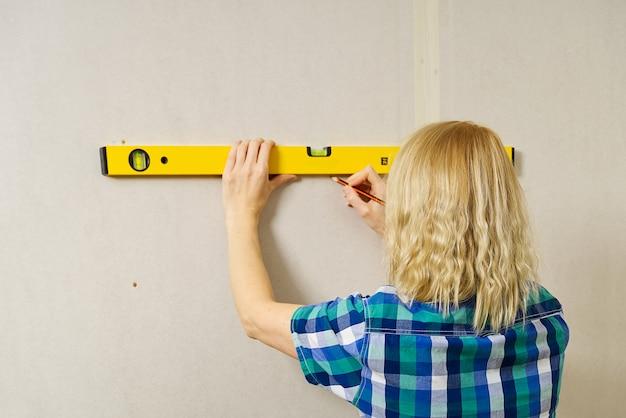 Сделай сам белокурая молодая привлекательная женщина, использующая спиртовой уровень, чтобы отработать измерения на стене из гипсокартона.