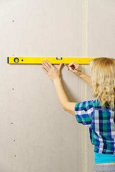 Diy 금발의 젊은 매력적인 여자는 정신 수준을 사용하여 석고 보드 벽에 측정을 계산합니다.