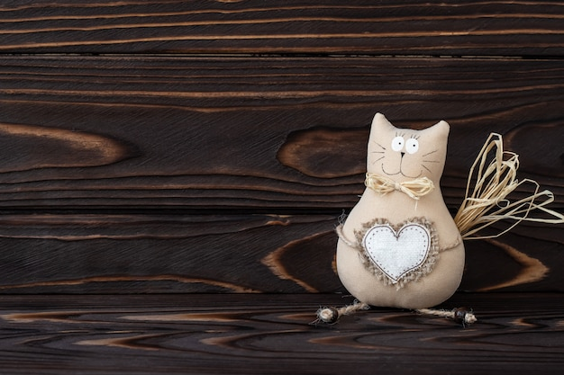 Diy, игрушка кота на деревянной предпосылке. ручная кошечка с сердцем из текстиля. темные деревянные натуральные доски, текстовое пространство. романтическая открытка, концепция любви. старинные украшения, детские игрушки.