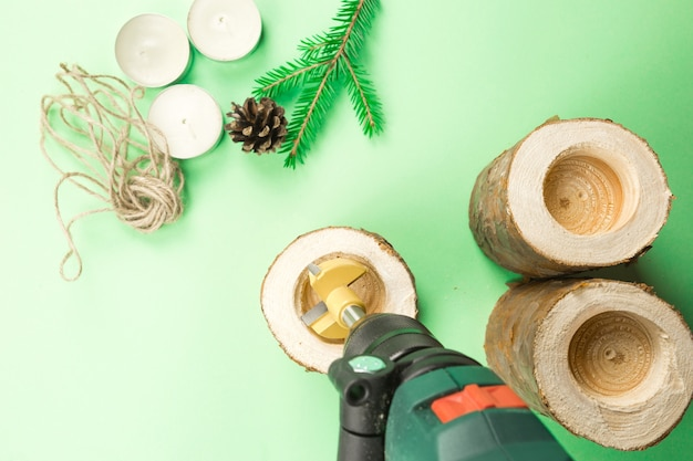 Diy christmas candle holder made of pine logs, candles, craft rope, fir branches and cones. a drill is a tool for manufacturing. drill holes. step-by-step instructions flat lay, step 2.