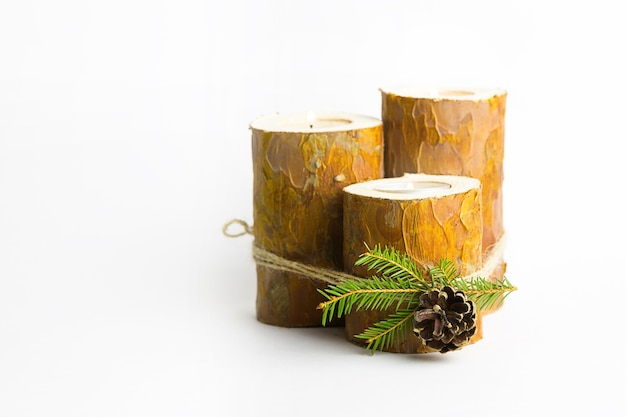 Diy christmas candle holder made of pine logs, candles, craft rope, fir branches and cones. finished product, insert candles and light. new year's decor. step-by-step instructions flat lay, step 5.