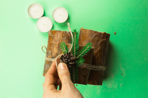 Diy christmas candle holder made of pine logs, candles, craft rope, fir branches and cones. hands attach the decoration. step-by-step instructions flat lay, step 4.