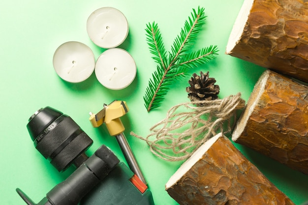 Diy christmas candle holder made of pine logs, candles, craft rope, fir branches and cones. layout on a green background. a drill is a tool for manufacturing. step-by-step instructions, step 1.