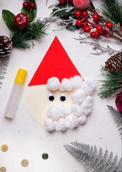 一歩一歩diyのクリスマスカード。白いコンクリートのテーブルに色紙と綿から。
