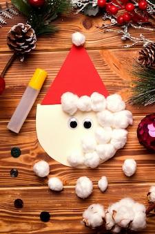 一歩一歩diyのクリスマスカード。色付きの紙と木製のテーブルの綿から。