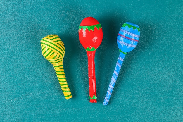 Diy cinco de mayo maracas from eggs, spoons and cereals on a green background.