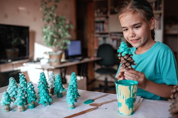 Diyクラフトギフトとクリスマスデコレーション。それが松の木であるかのようにコーンを着色する女の子、緑になります