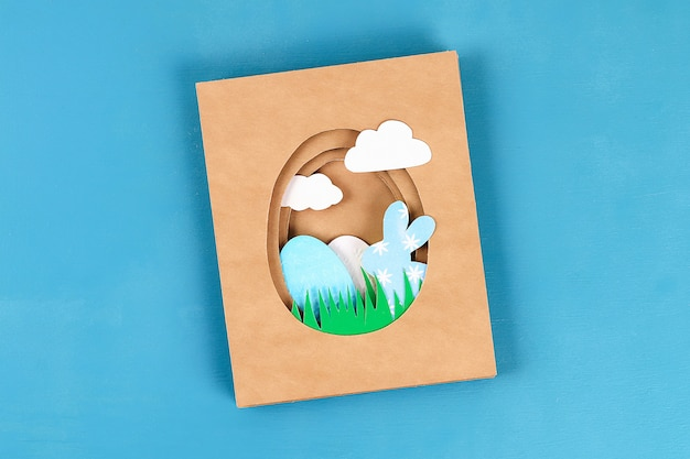 Diy easter cards from paper. volume greeting cards with a bunny, egg on blue background. 3d.