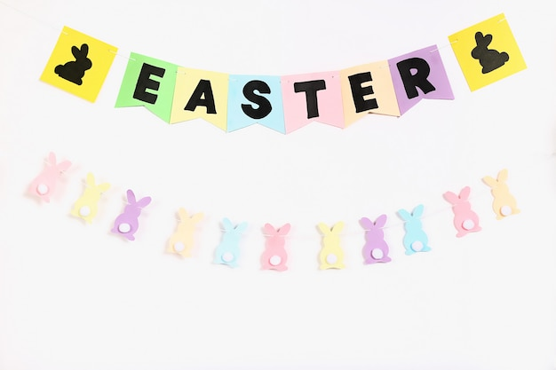 Diy easter garland bunnies, flags easter made paper white wall background
