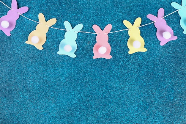Diy easter garland bunnies made paper blue background.