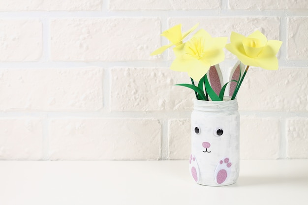 Diy easter vase bunny from glass jar, felt, googly eyes on a green background