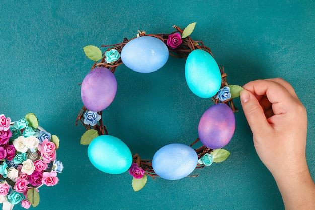 Diy easter wreath of twigs, painted eggs and artificial flowers on a green background.