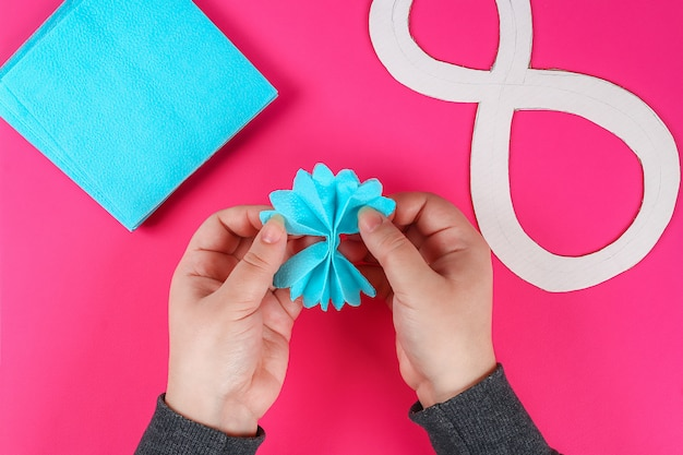 Diy eight made cardboard decorated artificial flower made blue tissue paper napkin pink background.