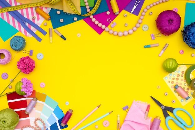 Diy。裁縫用具、はさみ、色糸、針、ピン、巻尺、コイル、ボタンのフレームを備えたフラットなレイアウト