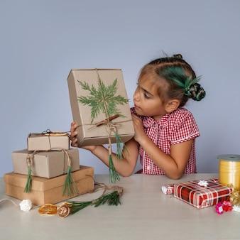 Сделай сам. девушка делает выбор между искусственной и экологически чистой рождественской упаковкой и подарками