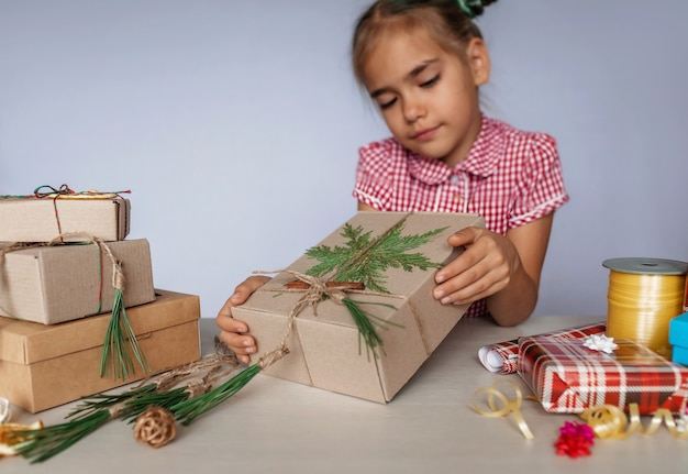 Diy。人工と環境に優しいクリスマスラッピングとギフトのどちらかを選択する女の子