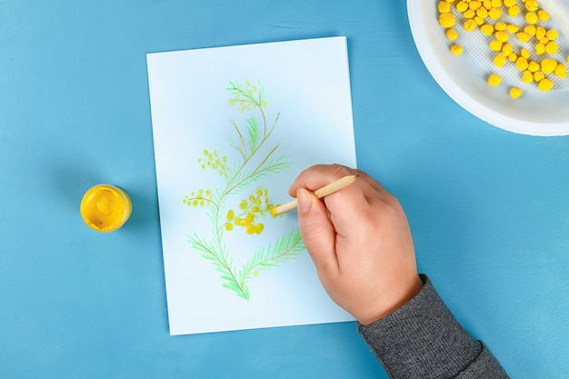 Diy greeting card with mimosa flowers paper balls for march 8 on blue background.