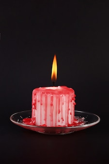 Diy halloween white candle covered in red wax like blood drops on black background